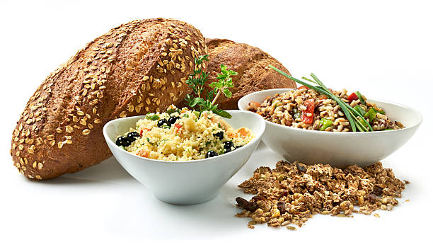 """Healthy Lifestyle, Whole grains """"Healthy eating. A variety of prepared dishes made with whole grains for a healthy lifestyle. Multigrain breads, granola with dried fruit, couscous salad with blueberries, brown rice with bell pepper salad. Shot on white with natural shadow."""" burwellphotography stock pictures, royalty-free photos & images"""