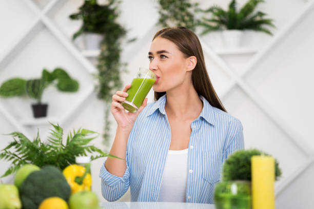zdrowy styl życia. kobieta pije smoothie w kuchni - detoks zdjęcia i obrazy z banku zdjęć