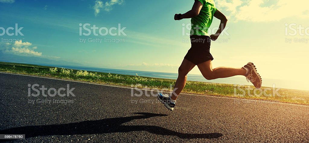 healthy lifestyle woman runner running on road stock photo
