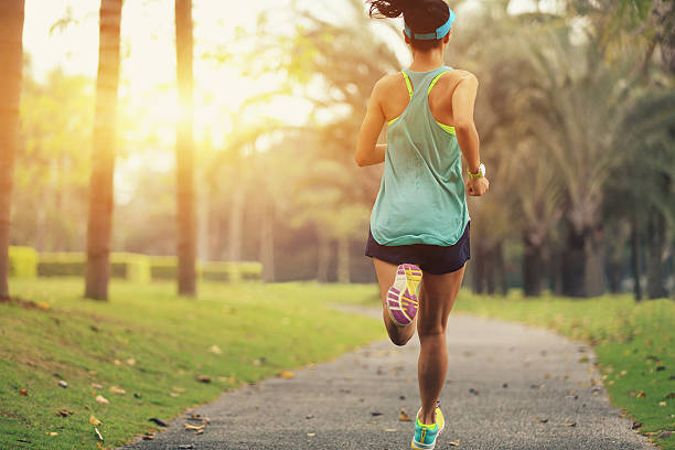 healthy lifestyle young sporty asian woman running at tropical park stock photo