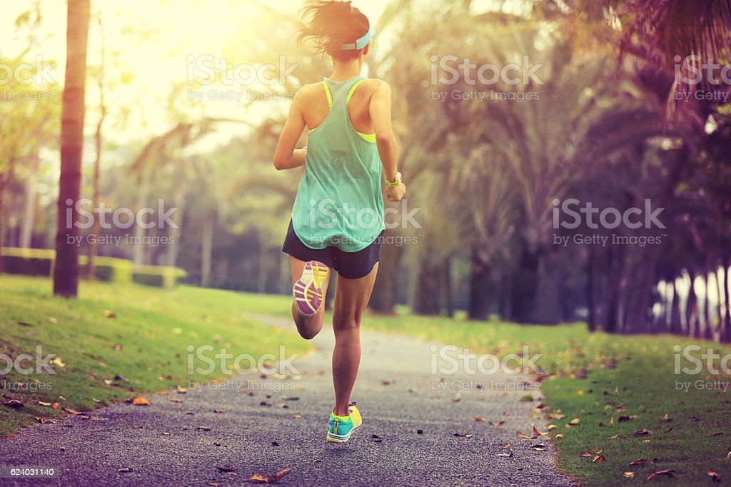 healthy lifestyle young sporty asian woman running at tropical park – zdjęcie