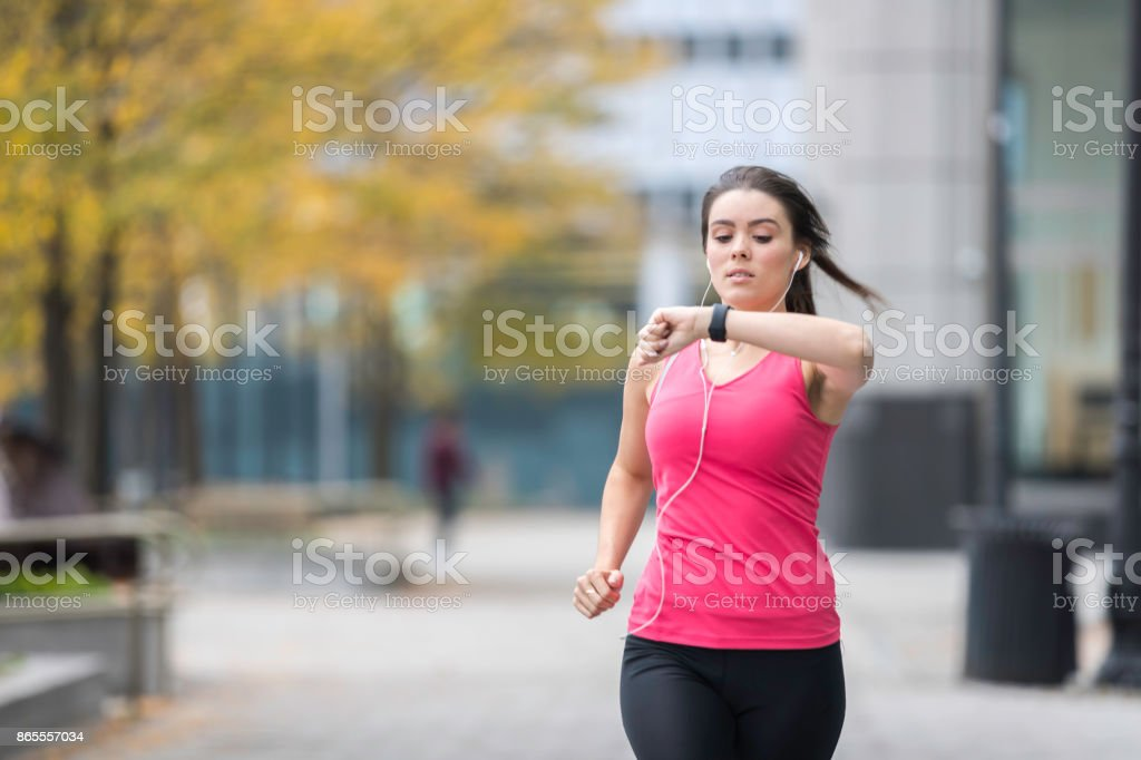 Healthy Lifestyle Young Woman Running and Looking at Smart watch stock photo