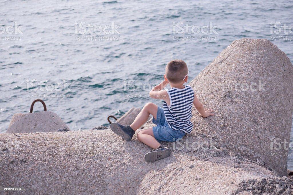 스트라이프 셔츠와 바다에 앉아 반바지 입은 건강 한 어린 소년 royalty-free 스톡 사진