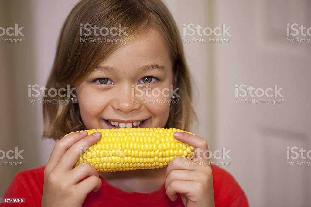 Healthy little girl eating corn cob vegetables indoors royalty-free stock photo