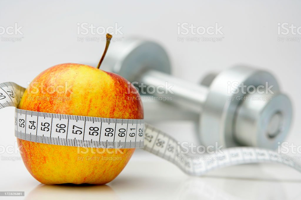 Healthy living concept showing a measuring tape around Apple royalty-free stock photo