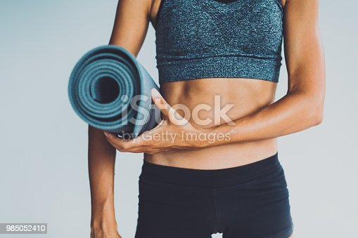 Healthy living- young woman with yoga mat