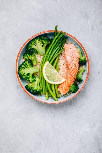 almuerzo saludable de salmón y brócoli con espárragos y arroz - dieta paleolítica fotografías e imágenes de stock