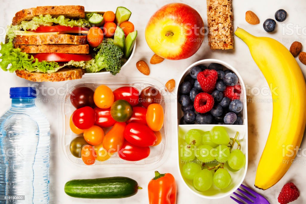 Healthy lunch box with sandwich and fresh vegetables, bottle of water and fruits stock photo