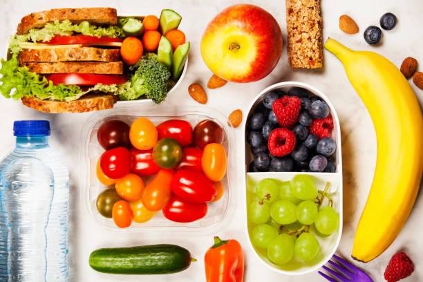 Caja de almuerzo saludable con sandwich y verduras frescas, botella de agua y frutas - foto de stock