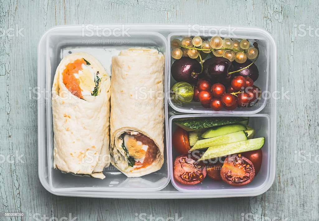 Healthy lunch box with vegetarian tortilla wraps, vegetables and fruits stock photo