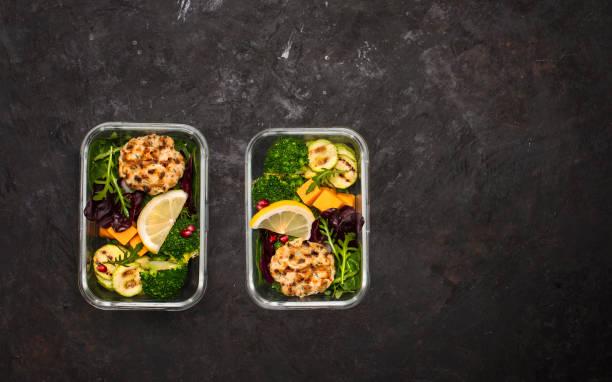 Gesunde Lunchboxen behältern mit gegrillten Hähnchenfleischbällchen, Brokkoli, Zucchini, Kürbis und Salat auf schwarzem Hintergrund. Gesundes Essen am Arbeitsplatz im Büro. – Foto