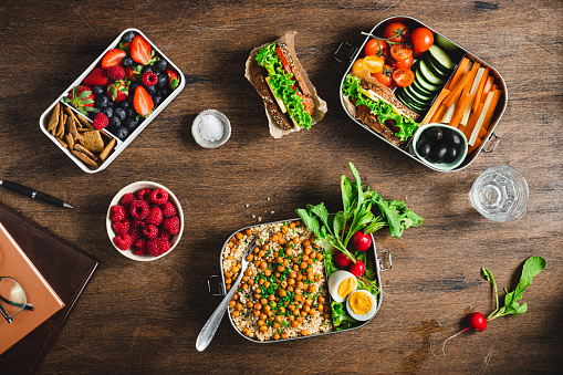 Top view of a healthy meal prep containers on wooden table. Cooked food with salad, fruits and berries in lunch boxes. flat lay. Food in boxes for school or office.