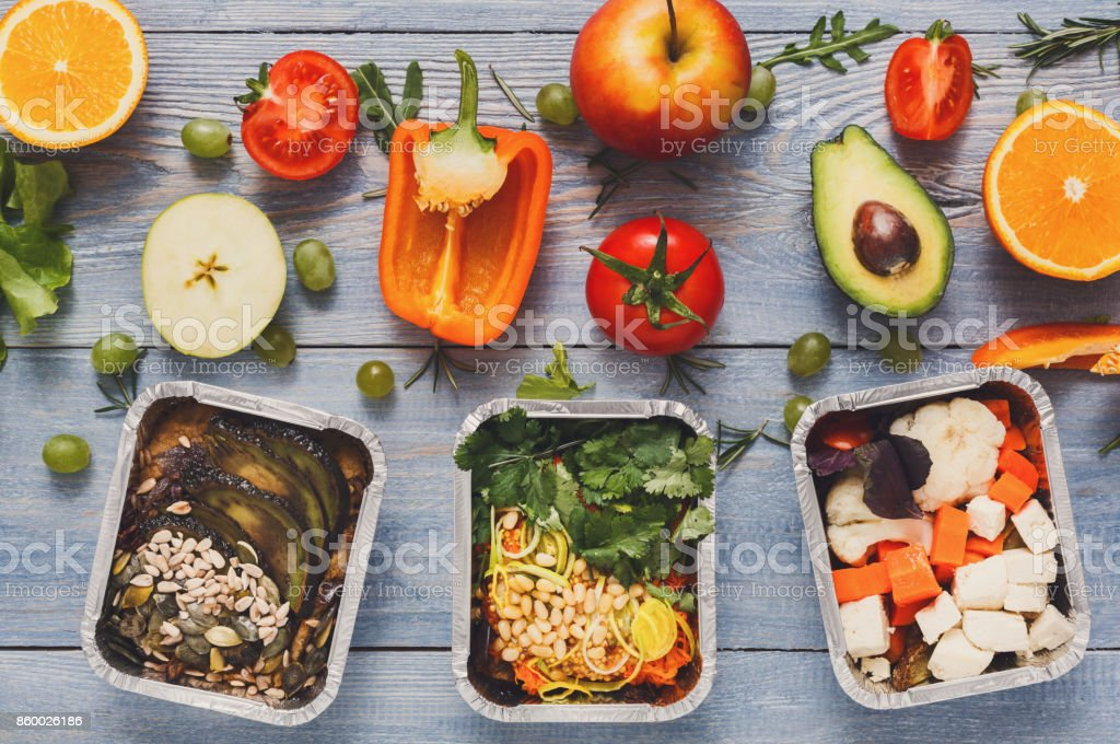 Healthy lunch in boxes with fresh vegetables on blue wood background stock photo