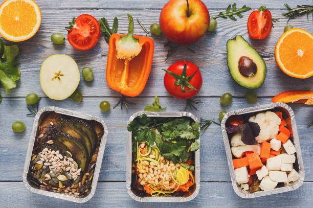 healthy lunch in boxes with fresh vegetables on blue wood background - tipo di cibo foto e immagini stock