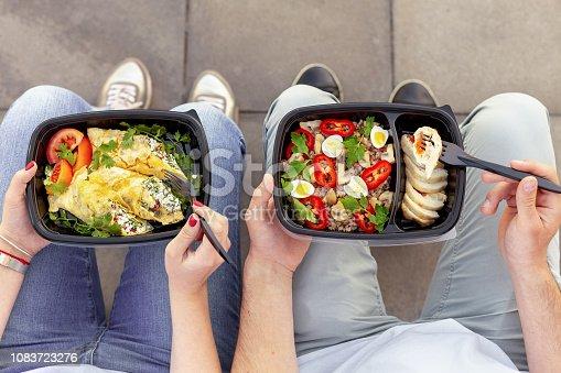 Couple enjoying take away healthy lunch outdoors, top view