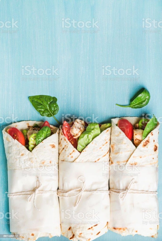 Healthy lunch snack. Three tortilla wraps with grilled chicken fillet and fresh vegetables over turquoise blue painted wooden background foto stock royalty-free