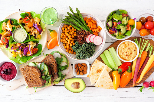 Healthy lunch table scene with nutritious lettuce wraps, Buddha bowl, vegetables, sandwiches, and salad. Overhead view over a white wood background.
