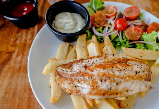 gesundes mittagessen mit gebratenem fisch, pommes und salat - englischer erbsen salat stock-fotos und bilder