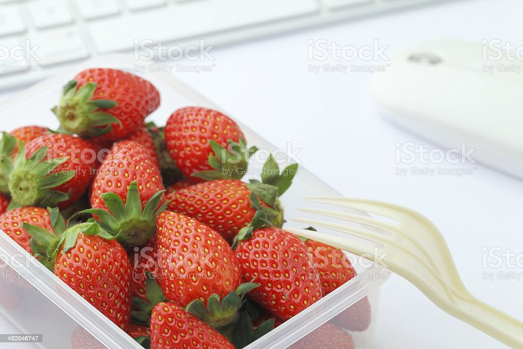 Healthy lunch with strawberry and blueberry mix in office royalty-free stock photo