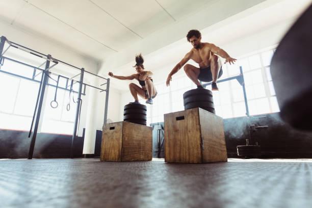 Caja de hombre y mujer saneada saltando en el gimnasio - foto de stock