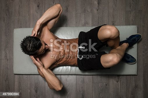 istock Healthy Man Doing Sit-Ups On Foor 497990394