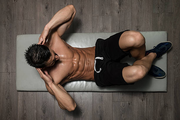 Healthy Man Doing Sit-Ups On Foor Healthy Man Exercising Abdominals On Foor abdominal muscle stock pictures, royalty-free photos & images
