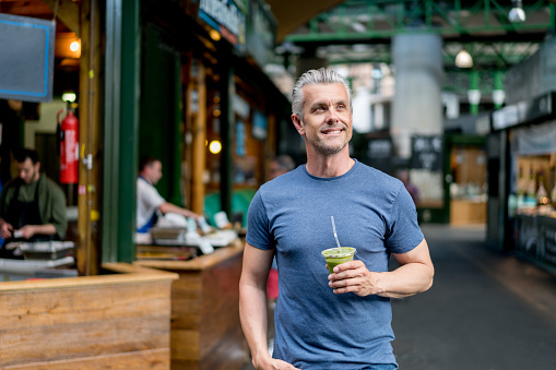Healthy man drinking a smoothie and walking on the street looking happy