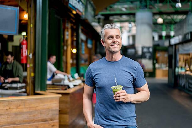 healthy man having a smoothie - 50 54 jaar stockfoto's en -beelden