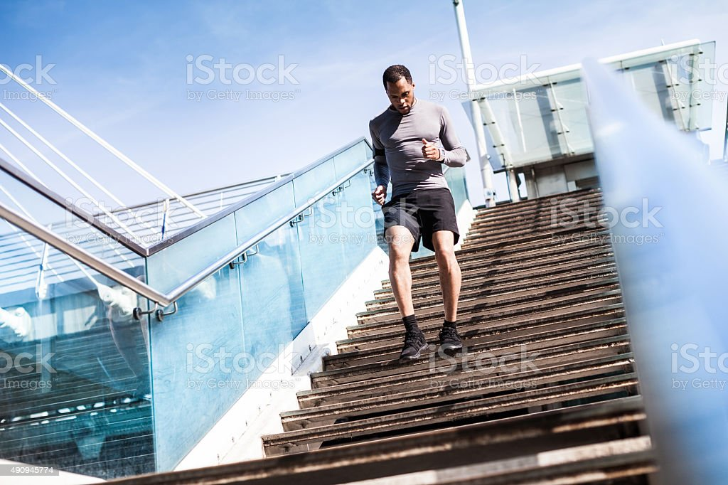 Healthy man running downhill on steps stock photo