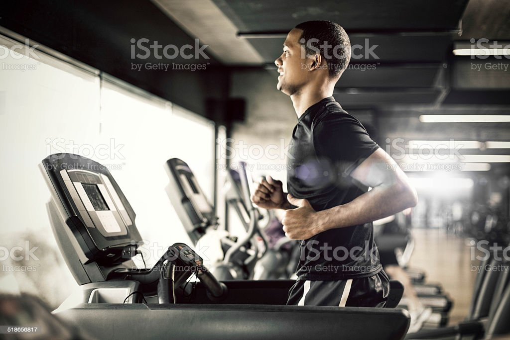Healthy man Running on Treadmill stock photo