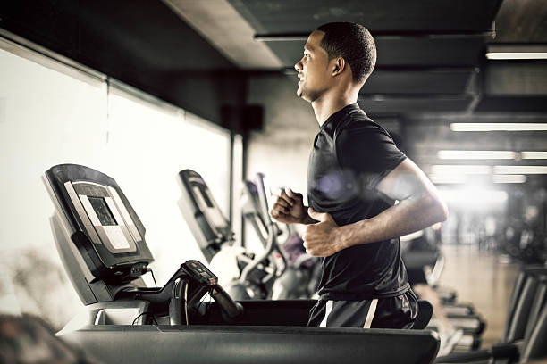 Healthy man Running on Treadmill Healthy young man in GYM running on treadmill exercise machine stock pictures, royalty-free photos & images