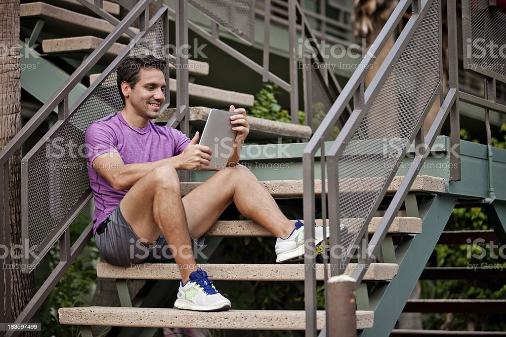 Healthy man sitting on stairs with tech royalty-free stock photo