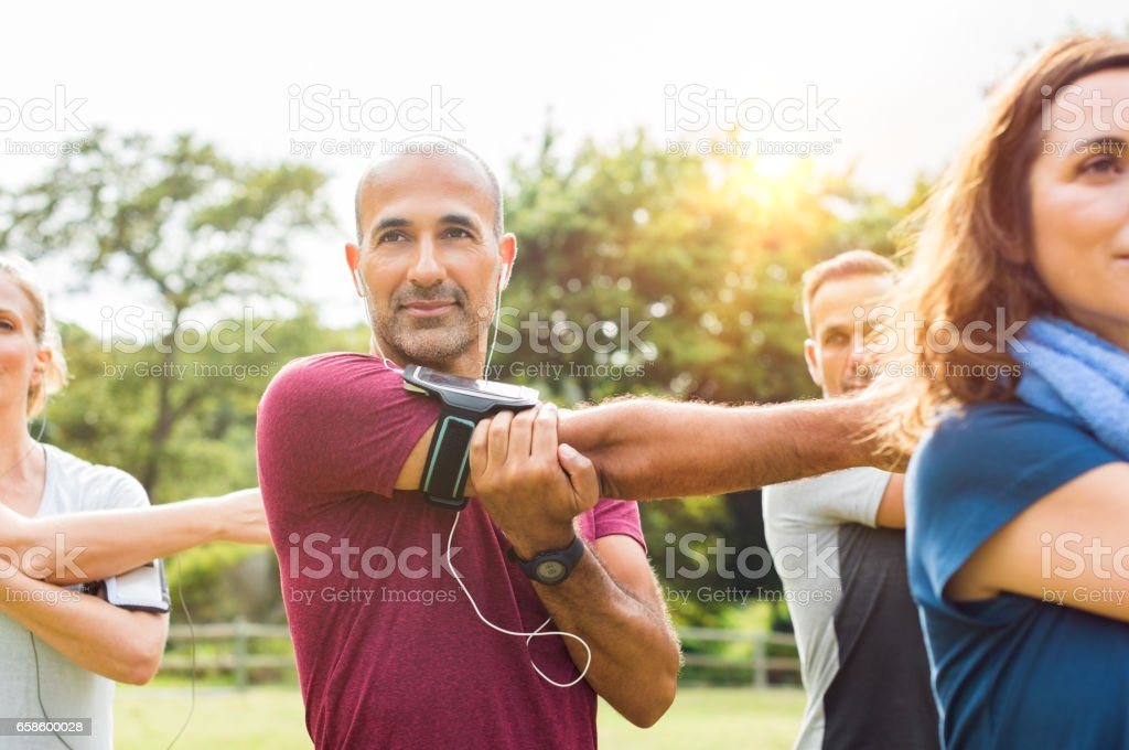 Healthy mature man stretching arm stock photo