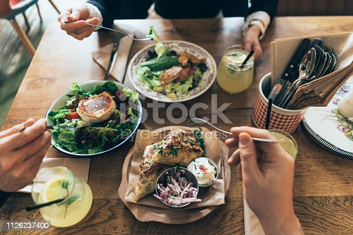 Table with Healthy Meal with salad, cheese, avocado, white meat and lemonade