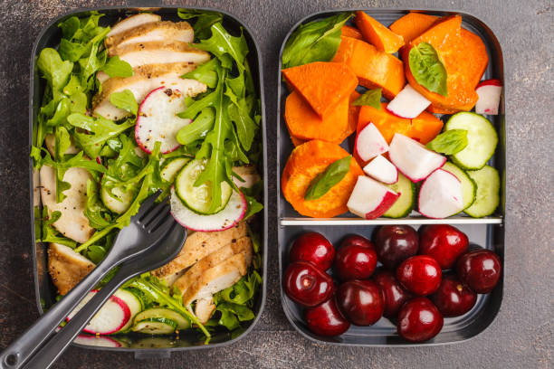 Healthy meal prep containers with grilled chicken with salad, sweet potato, berries, fruits and vegetables. Dark background, top view. stock photo
