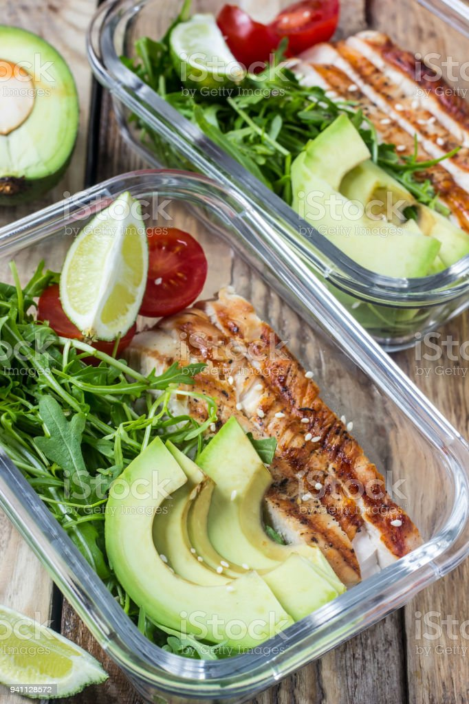 Healthy meal prep containers with rukola, turkey grill, tomatoes and avocado stock photo