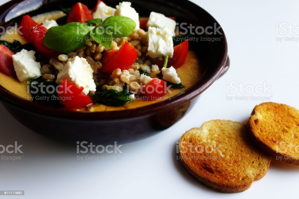 Healthy meals bowl of mashed chick peas barely spinach feta cheese and cherry tomatoes stock photo