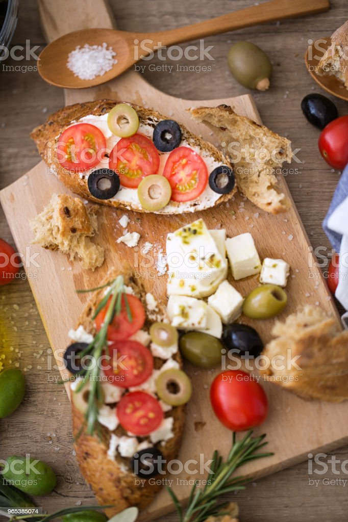 healthy Mediterranean bruschetta on wooden cutting board with vegetables royalty-free stock photo