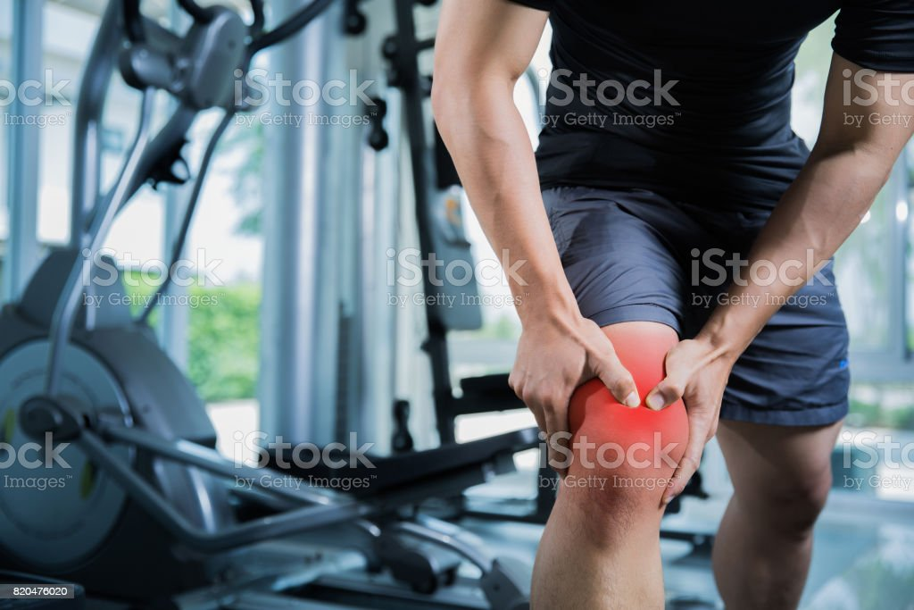Healthy men Injury from exercise in the gym, he injured his knee stock photo