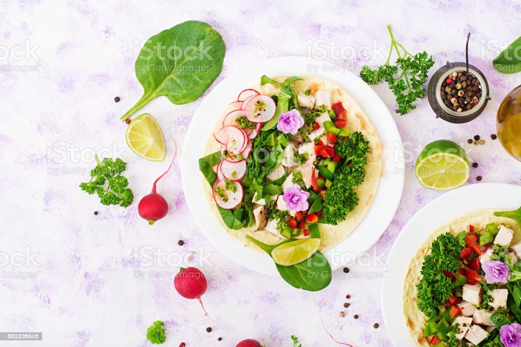 Healthy mexican corn tacos with boiled chicken breast, spinach, radish and paprika. Flat lay. Top view royalty-free stock photo