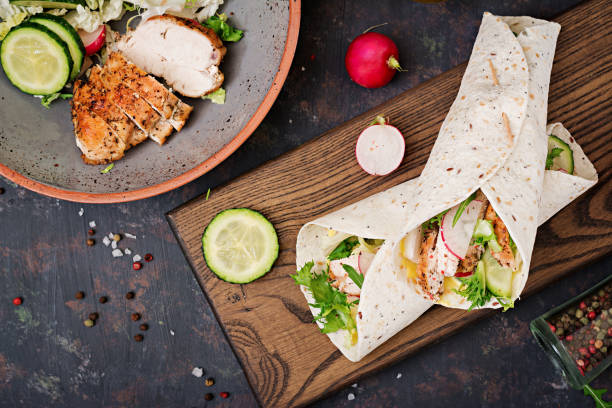 healthy mexican tacos with baked chicken breast, cucumber, radish and lettuce. flat lay. top view - avvolto foto e immagini stock