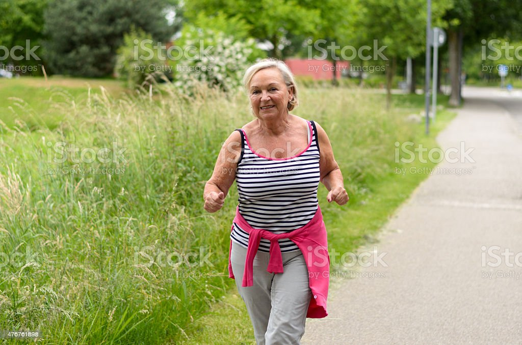 Healthy Middle Aged Woman Jogging at the Street stock photo
