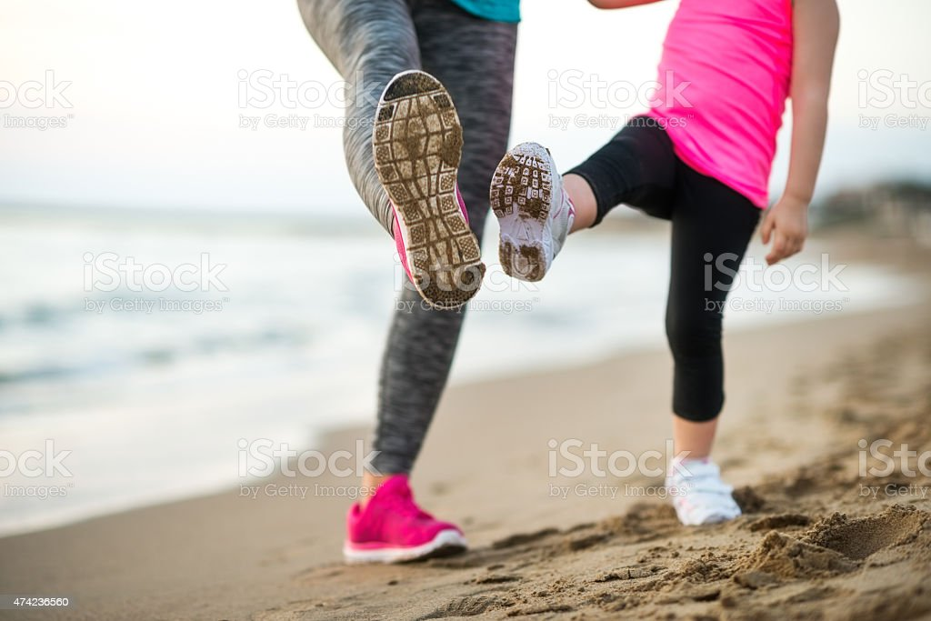 Healthy mother and baby girl workout on beach. Closeup stock photo