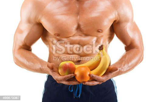 istock healthy muscular man holding a fresh fruits, isolated on white 495670067
