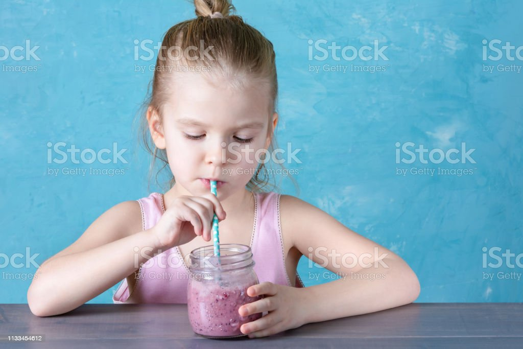 Healthy natural drink, healthy food. The child drinks a berry fruit...