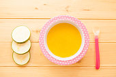 Healthy natural eco baby lure. Soup of squash, carrot, onion, cabbage, potato in plate and with spoon on wooden background with copy space