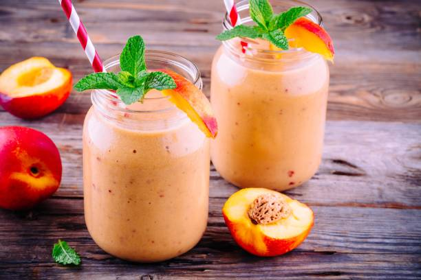 Healthy nectarine smoothies in a mason jar with mint on wooden background stock photo
