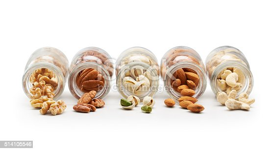 Healthy nuts pouring out from bottle isolated on white