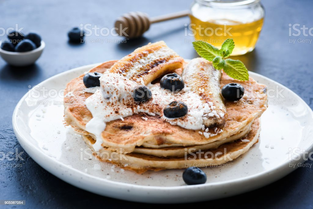 Healthy oat pancakes with banana, blueberries and yogurt stock photo