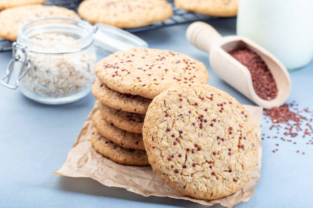 Healthy oatmeal and red quinoa cookies on table and cooling rack served with milk, horizontal stock photo